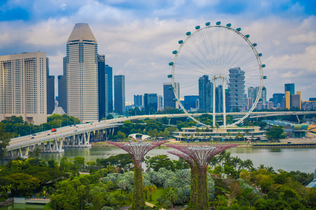 SINGAPORE, SINGAPORE - FEBRUARY 01, 2018: Beautiful outdoor view of Singapore Flyer - the Largest Ferris Wheel in the World with a bridge and huge buildings in the horizont, located in Singapore