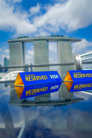 SINGAPORE, SINGAPORE - JANUARY 30, 2018: Close up of informative sign of table reserved with a visa logo, with a blurred three towers of the Marina Bay Sands Ressort, the worlds most expensive standalone casino at the time of opening in 2010, in Singapore