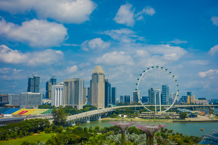 SINGAPORE, SINGAPORE - FEBRUARY 01, 2018: Beautiful above view of Singapore Flyer - the Largest Ferris Wheel in the World with a bridge and huge buildings in the horizont, in a cloudy day, located in Singapore