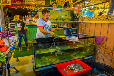 AO NANG, THAILAND - MARCH 05, 2018: Unidentified people inside of a restaurant, and a fish tak with lobsters ready to cook at Ao Nang town