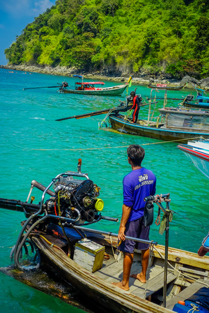 AO NANG, THAILAND - MARCH 05, 2018: Close up of unidentified man in the boat close to a motor with a gorgeous turquoise water in the chicken island in Thailand