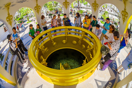 CHIANG RAI, THAILAND - FEBRUARY 01, 2018: Indoor view of unidentified people inside of a building and coin well at the White Temple in Chiang Rai, coins under water in White Temple