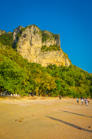 Outdoor view of unidentified people walking in the beach with a mountain in the horizont, Andaman Sea, South of Thailand
