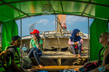 AO NANG, THAILAND - MARCH 05, 2018: Outdoor view of unidentified people inside of fishing thai boats at the shore of Po-da island, Krabi Province, Andaman Sea, South of Thailand