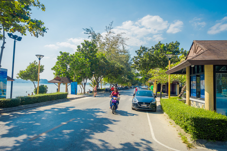 AO NANG, THAILAND - FEBRUARY 09, 2018: Outdoor view of some cars parked at one side of the road and unidentified woman riding a motorcycle close to local shops at Ao Nang beach