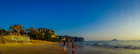 AO NANG, THAILAND - MARCH 05, 2018: Panoramic view of unidentified people walking in the beach with a mountain in the horizont, Andaman Sea, South of Thailand 報道画像