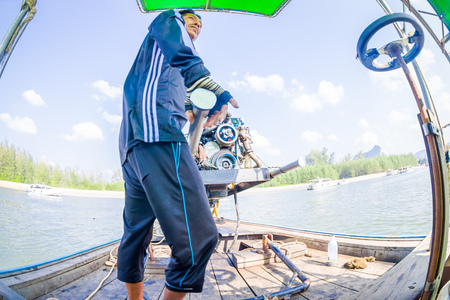 AO NANG, THAILAND - FEBRUARY 09, 2018: Close up of unidentified man manipulating a boat motor with a blurred nature background