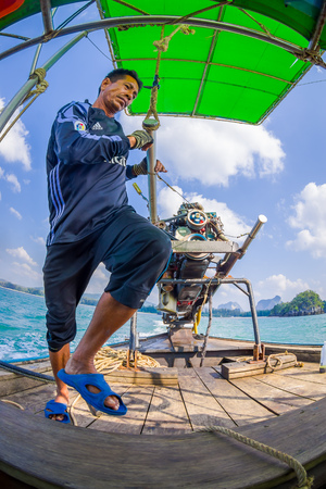 AO NANG, THAILAND - FEBRUARY 09, 2018: Outdoor view of unidentified man manipulating a boat motor with a blurred nature background