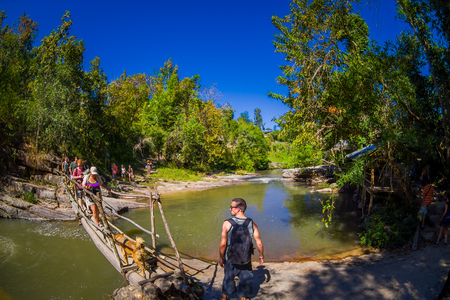 CHIANG RAI, THAILAND - FEBRUARY 01, 2018: Outdoor view of unidentified people walking in tropical rainforest using a wooden bridge over a small river in Chiang Mai Province, Thailand Editorial
