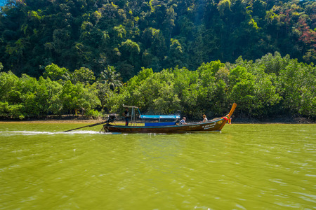 AO NANG, THAILAND - FEBRUARY 19, 2018: Outdoor view of long tail fishing boat sailing in the water with tourists in the river at Krabi Province, South of Thailand