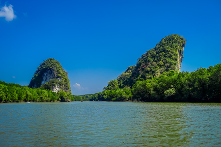 Beautiful outdoor view of huge mountains in the horizont, viewed from the river during a gorgeopus blue asky in Krabi Province, South of Thailand