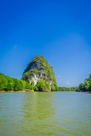 タイ南部クラビ県のゴルゲオプスブルーアスキーの間に川から見た地平線の巨大な山々の美しい屋外ビュー 写真素材 - 97385823