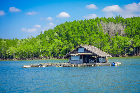 Outdoor view of old and damaged house floating in the river close to the mangroves in a gorgeopus blue asky in Krabi Province, South of Thailand