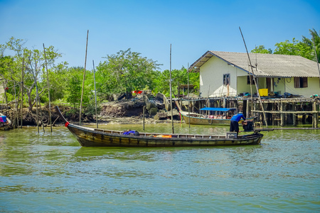 AO NANG, THAILAND - FEBRUARY 19, 2018: Outdoor view of long tail fishing boats in the river close to a old buildings located in the river in fish farms at Krabi Province, South of Thailand