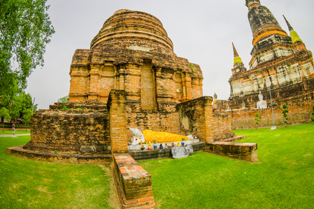 Outdoor view of stoned budha with a yellow fabric and dome behind at Wat Pra. It was the holiest temple of the city until it was destroyed in year 1767