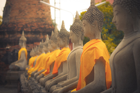 Close up of Ancient Buddha Statue in a row with a yellow fabric at WAT YAI CHAI MONGKOL, The Historic City of Ayutthaya, Thailand