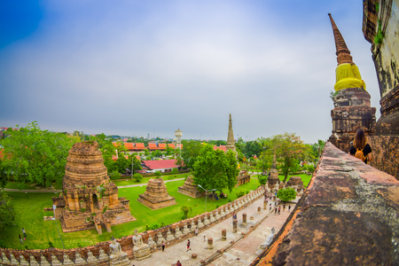 Beautiful landscape with some unidentified people walking at stupa ancient buddhist temple, famous and major tourist attraction religious of Ayutthaya Historical Park in Thailand