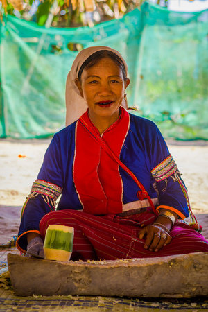 CHIANG RAI, THAILAND - FEBRUARY 01, 2018: Outdoor view of unidentified woman with a knife in her hand to do a handycraf with bamboo cane at Long Neck hill tribe village Kayan Lahwi, in Chiang Mai