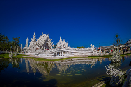 Panoramic view of white church of Wat Rong Khun temple in Chiangrai, Thailand, reflected in the water