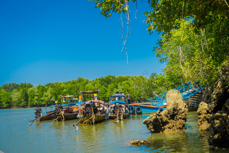AO NANG, THAILAND - FEBRUARY 19, 2018: Long tail fishing boats in the riverside close to metallic structure in the pier located in the river at Krabi Province, South of Thailand