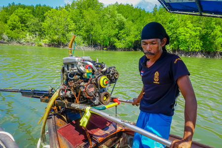 AO NANG, THAILAND - FEBRUARY 09, 2018: Unidentified man manipulating a boat motor of long fisihng boat with a nature background
