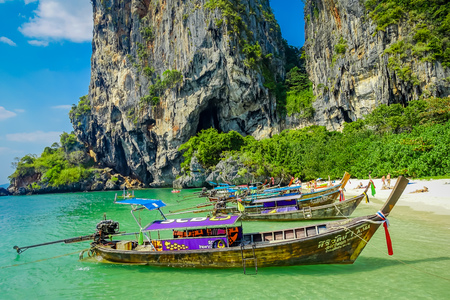 PHRA NANG, THAILAND - FEBRUARY 09, 2018: Beautiful outdoor view of long tail boats in a row in the shore of Phra nang island in a gorgeous sunny day and turquoise water