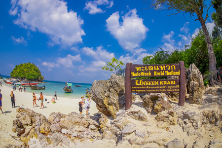 TUP, THAILAND - FEBRUARY 09, 2018: Outdoor view of informative sign written in a wooden structure in the rocks on Tup island with a gorgeous sunny day and turquoise water