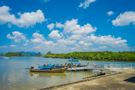 AO NANG, THAILAND - FEBRUARY 19, 2018: Outdoor view of long tail fishing boats in the riverside close to metallic structure in the pier located in the river at Krabi Province, South of Thailand 報道画像