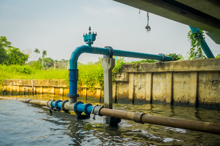 Outdoor view of blue pipeline conection under a bridge on Chao Phraya river. Thailand, Bangkok Stock Photo