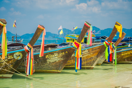 PODA, THAILAND - FEBRUARY 09, 2018: Outdoor view of long tail boats in a row at shore on Poda island in a gorgeous sunny day and turquoise water