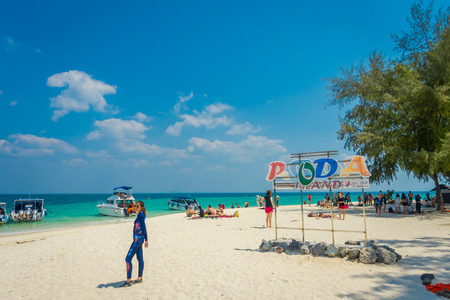 PODA, THAILAND - FEBRUARY 09, 2018: Outdoor view of unidentified people posing for a pictures in front of informative sign over the white sand on Poda island in a gorgeous sunny day