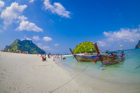 TUP, THAILAND - FEBRUARY 09, 2018: Beautiful outdoor view of unidentified people in the beach close to a long tail boats in a shore on Tup island in a gorgeous sunny day and turquoise water Editorial