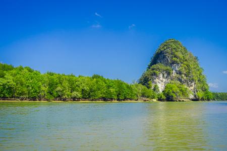 タイ南部クラビ県のゴルゲオプスブルーアスキーの間に川から見た地平線の巨大な山々の美しい屋外ビュー 写真素材 - 97907216