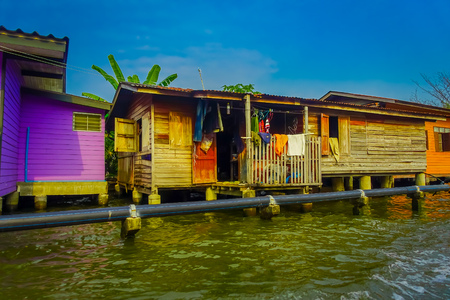Outdoor view of gorgeous floating wooden house with a pipeline on the Chao Phraya river. Thailand, Bangkok