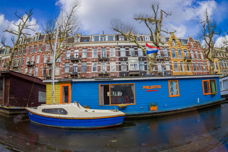 AMSTERDAM, NETHERLANDS, MARCH, 10 2018: Beautiful outdoor view of houseboats and apartment buildings behind on a canal in the city of Amsterdam