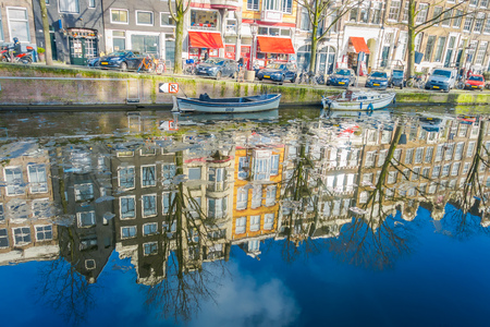 AMSTERDAM, NETHERLANDS, MARCH, 10 2018: Gorgeous view of reflecting building over river Amstel landmark in old european city spring landscape Editorial