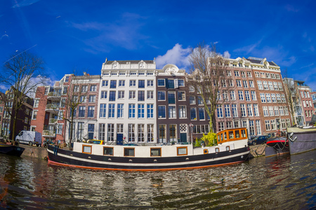 AMSTERDAM, NETHERLANDS, MARCH, 10 2018: Beautiful outdoor view of houseboats and apartment buildings on a canal in the city of Amsterdam