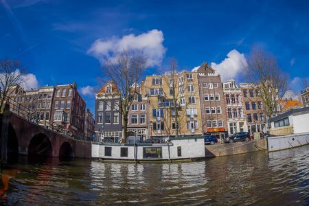 AMSTERDAM, NETHERLANDS, MARCH, 10 2018: Outdoor view of houseboats and apartment buildings on a canal in the city of Amsterdam