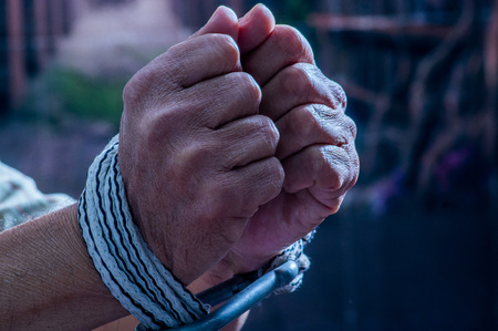 Close up of man hands wrapped with rope around wrists in captivity , victim abused, slave of work, respect for human rights and exploitation concept isolated on blurred background