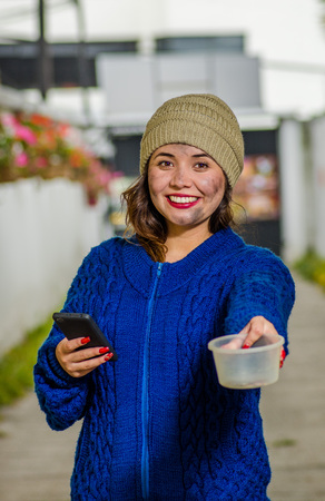 Outdoor view of homeless sad woman on the street in cold autumn weather holding an empty plastic flask in her hands asking for money, using a cellphone at sidewalk Stock Photo