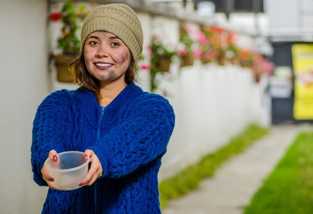 Outdoor view of homeless smiling woman begging on the street in cold autumn weather sholding an empty plastic flask in her hands asking for money, at sidewalk