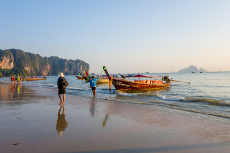 AO NANG, THAILAND - MARCH 05, 2018: Outdoor view of unidentified people walking in the beach close to Fishing thai boats at Po-da island, Krabi Province, Andaman Sea, South of Thailand