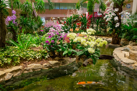 Indoor view of people walking in a small garden with plants inside of Singapore Changi Airport. Singapore Changi Airport is the primary civilian airport