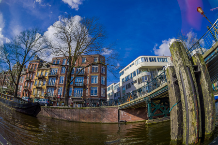 AMSTERDAM, NETHERLANDS, MARCH, 10 2018: Beautiful outdoor view of apartment buildings with abridge over a canal in the city of Amsterdam Editorial