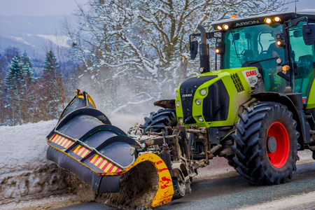 Valdres, Norway - March 26, 2018: Snow-removing machine cleans the street of the road from the snow in the morning snow-covered trees and roads in Norway