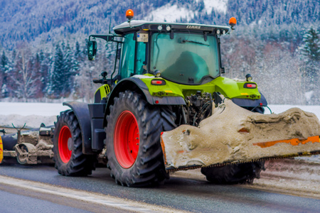 Valdres, Norway - March 26, 2018: Outdoor view of snow-removing machine cleans the street of the road from the snow in the morning snow-covered trees and roads in Norway Editorial