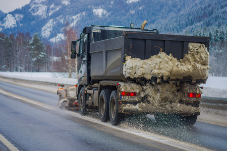 Reinli, Norway - March 26, 2018: Outdoor view of snow-removing machine cleans the street of the road from the snow in the morning snow-covered trees and roads in Norway
