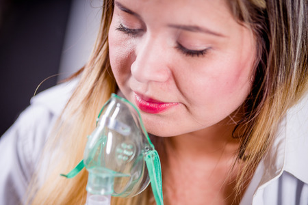 Portrait of young woman using nebulizer for asthma and respiratory diseases at home