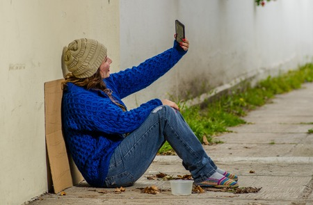 Quito, Ecuador, Narch, 26, 2018: Outdoor view of homeless woman begging on the street in cold autumn weather sitting on the floor at sidewalk taking a selfie