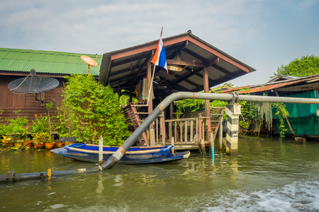 BANGKOK, THAILAND - MARCH 23, 2018: Outdoor view of floating wooden house with a pipeline on the Chao Phraya river. Thailand, Bangkok
